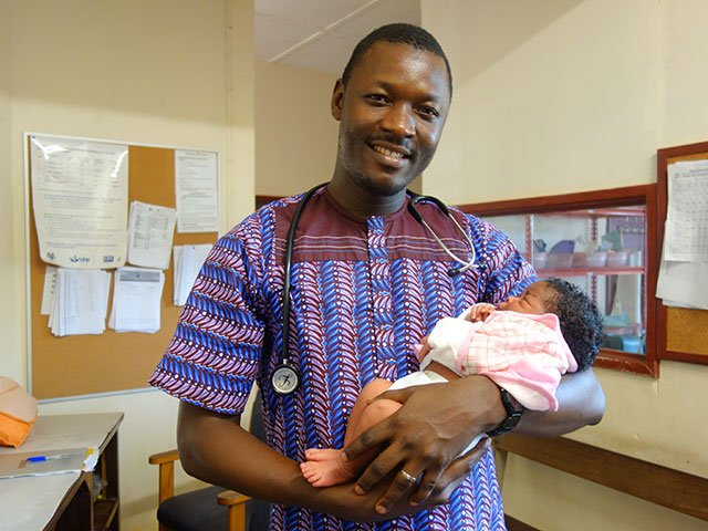 Egbe doctor holding a baby