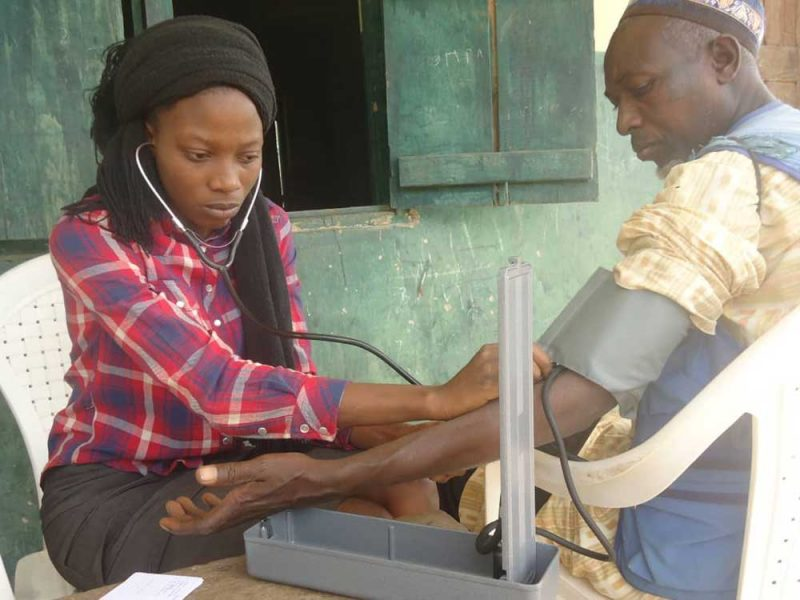 Egbe doctor taking patient's blood pressure